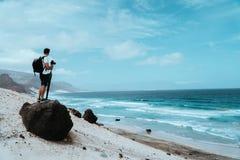 Viajante com câmera que fica no pedregulho vulcânico preto e que admira a paisagem estéril incomum da praia de Baia DAS Gatas fotografia de stock royalty free