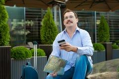 Viajante com plano do telefone celular e da cidade Imagens de Stock