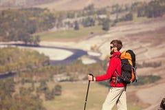 Viajante com a trouxa que caminha nas montanhas rochosas do verão Fotografia de Stock Royalty Free