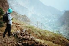 Viajante com trouxa que fica na borda do trajeto que conduz com a paisagem rural com montanhas, na maneira de fotos de stock royalty free