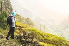 Viajante com trouxa que fica na borda do trajeto que conduz com a paisagem rural com montanhas, na maneira de imagem de stock royalty free