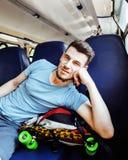 Viajante consideravelmente moderno do indivíduo do moderno dos jovens no trem com skateboa Fotos de Stock Royalty Free