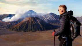 Viajante contra o nascer do sol fantástico no vulcão de Bromo indonésia Java islan foto de stock