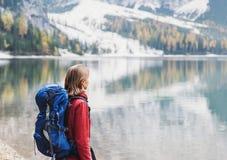 Viajante da jovem mulher nas montanhas dos cumes que olham em um lago Curso, inverno e conceito ativo do estilo de vida foto de stock