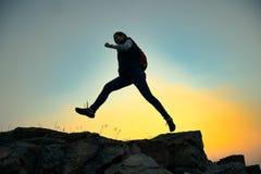 Viajante da jovem mulher que salta com a trouxa em Rocky Trail no por do sol morno do verão Conceito do curso e da aventura imagem de stock