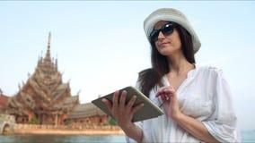 Viajante da jovem mulher que usa o guia digital app da leitura do tablet pc que procura a informação vídeos de arquivo