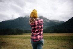 viajante da menina no chapéu com a trouxa que olha nuvens nas montanhas imagens de stock