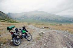 Viajante da motocicleta com as malas de viagem que estão na estrada rochosa extrema em um vale da montanha no tempo nebuloso fotografia de stock