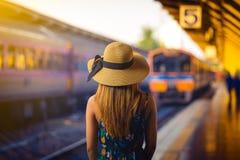 Viajante da mulher com o chapéu perto das trilhas de estrada de ferro que esperam o trem fotos de stock