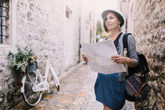 Viajante da mulher com o mapa na cidade velha Budva perto da bicicleta do vintage imagem de stock