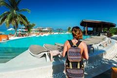 Viajante da mulher com a trouxa perto da piscina na ilha tropical fotografia de stock royalty free