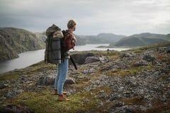Viajante da mulher com a trouxa que caminha nas montanhas Fotos de Stock