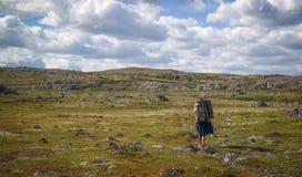 Viajante da mulher com a trouxa que caminha nas montanhas Imagens de Stock Royalty Free