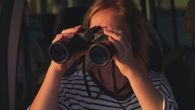 Viajante da mulher que olha através dos binóculos de uma janela de carro video estoque