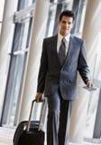 Viajante de negócio que puxa a mala de viagem e o passaporte Imagens de Stock