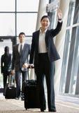 Viajante de negócio que puxa a mala de viagem e a ondulação Imagem de Stock Royalty Free