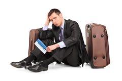 Viajante de negócio triste assentado ao lado de uma mala de viagem Fotografia de Stock Royalty Free