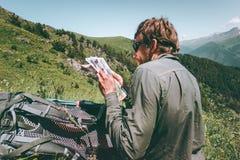 Viajante do homem com maneira do achado da rota do mapa de caminhar na aventura do estilo de vida do curso das montanhas imagens de stock