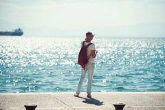Viajante do homem com a trouxa que olha longe na água do mar conceito do curso e do desejo por viajar férias e aventuras de verão imagens de stock