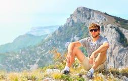 Viajante do homem novo que relaxa com as montanhas no fundo Imagens de Stock