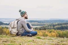 Viajante do homem novo que senta-se sobre o monte curso e conceito ativo do estilo de vida foto de stock royalty free