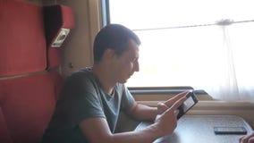 Viajante do homem que relaxa no trem que escuta a música e que sorri através das imagens através dos meios sociais do estilo de v filme