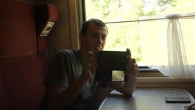 Viajante do homem que relaxa no trem que escuta a música e que sorri através das imagens através dos meios sociais vídeo de movim video estoque