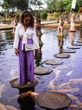 Viajante fêmea de solo que alimenta Koi Fish em alpondras em torno de Koi Fish na fonte principal em Tirta Gangga, Bali imagens de stock royalty free