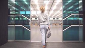 Viajante fêmea do passageiro que verifica a informação do bilhete da passagem de embarque e na placa da programação que prepara-s filme