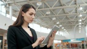 Viajante fêmea novo do passageiro no aeroporto usando seu tablet pc ao esperar o voo, mulher de negócio em seguida Imagens de Stock
