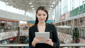 Viajante fêmea novo do passageiro no aeroporto usando seu tablet pc ao esperar o voo, mulher de negócio em seguida Fotografia de Stock