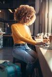 Viajante fêmea que trabalha no portátil que senta-se em um restaurante foto de stock royalty free
