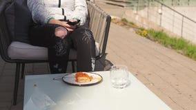 Viajante feliz que come a sobremesa doce em um restaurante - cabelo marrom ondulado do bolo, luz vestindo da mulher f?mea caucasi video estoque