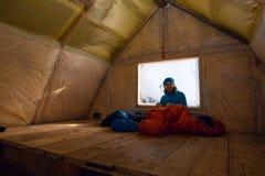 Viajante feliz, restos da mulher na cabana velha da montanha imagens de stock royalty free