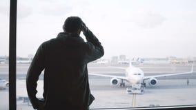 Viajante masculino com o saco grande no ombro que anda acima à janela terminal da sala de estar do aeroporto para apreciar a vist video estoque