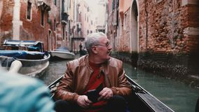 Viajante masculino europeu superior excitado no sorriso da gôndola, olhando ao redor na viagem bonita da excursão da excursão do  filme