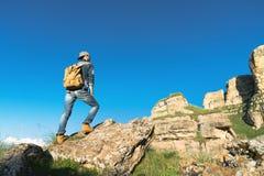 Viajante masculino farpado à moda nos óculos de sol e em um tampão com uma trouxa em um terno da sarja de Nimes e em suportes ama fotos de stock royalty free