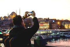 Viajante masculino novo que fotografa uma vista bonita do Bosphorus em Istambul Imagem de Stock Royalty Free