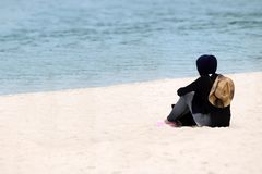 Viajante muçulmano da menina no hijab que senta-se na praia fotos de stock