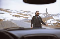 Viajante na estrada rural que tenta parar um carro fotografia de stock royalty free