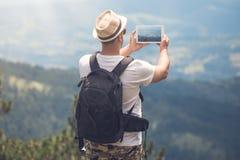 Viajante novo com a trouxa que toma fotos da paisagem bonita foto de stock royalty free