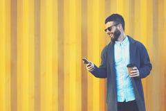 Viajante novo do blogger do moderno em um revestimento da sarja de Nimes usando o smartphone e o Internet 4G modernos Fotos de Stock Royalty Free