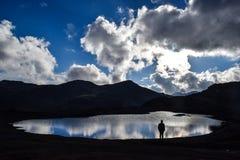 Viajante observando a lagoa que olha como um espelho foto de stock royalty free