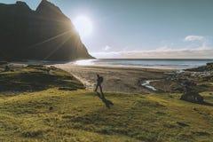Viajante que anda ao longo de uma praia de Lofoten no por do sol imagem de stock