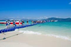 Viajante que anda na ponte da caixa plástica à ilha coral Fotos de Stock Royalty Free