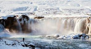 Viajante que está na queda da água de Godafoss no inverno foto de stock