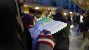 Viajante que guarda o mapa da cidade nas mãos, olhando as lojas de lembrança, verificando a rota video estoque