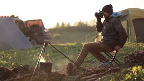 Viajante que senta-se ao lado da fogueira e que toma a foto através da câmera profissional video estoque