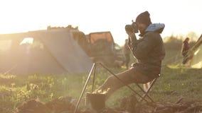 Viajante que senta-se ao lado da fogueira e que toma a foto através da câmera profissional vídeos de arquivo