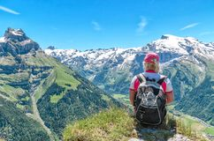 Viajante que senta-se em um penhasco com uma trouxa que admira o mountai foto de stock royalty free